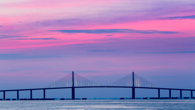 Brilliant sunrise lights up the sky behind Sunshine Skyway Bridge, St. Petersburg, Florida.