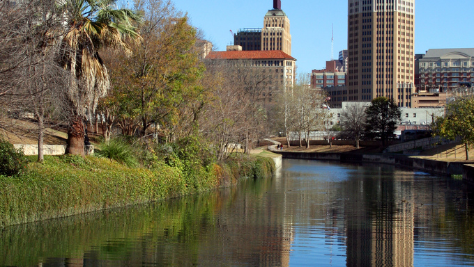 A riverwalk reflection of a tower in the San Antonio skyline.