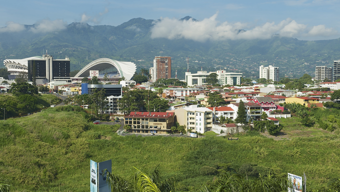 View of the National Stadium and buildings with mountains at the background in San Jose, Costa Rica.