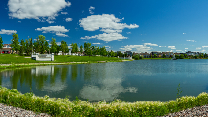 Beautiful pond with estate homes in the background in Winnipeg. Canada