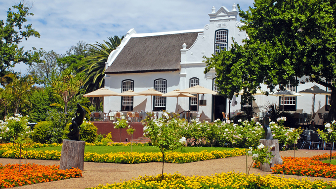 Beautiful landscape with colonial farm house, patio and flowers in the garden(South Africa)