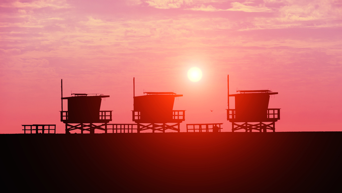 Lifeguard towers on the beach at sunset.