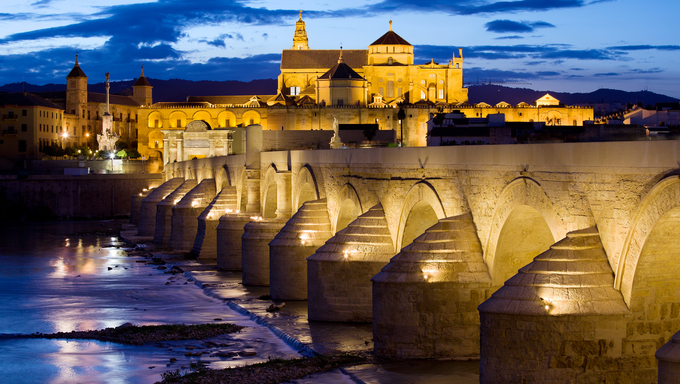 Roman Bridge on Guadalquivir river and Mosque Cathedral (La Mezquita) illuminated at dusk in the city of Cordoba, Andalusia, Spain.