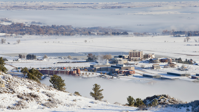 Foothills of Fort Collins, Colorado with university building and solar farm. A winter scenery with snow and fields of fog.