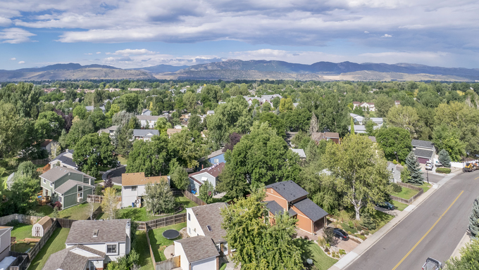 Aerial panorama of residential area in Fort Collins, Colorado, with foothills of Rocky Mountains and Horsetooth Rock in the background.