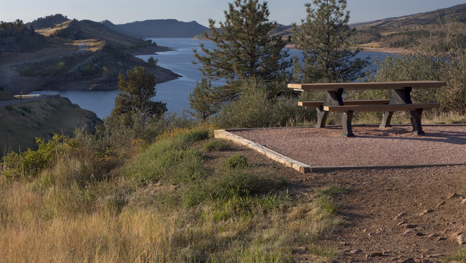 Picnic table on shore of mountain lake (Horsetooth Reservoir) near Fort Collins, Colorado at foothills of Rocky Mountains, early morning in the fall.