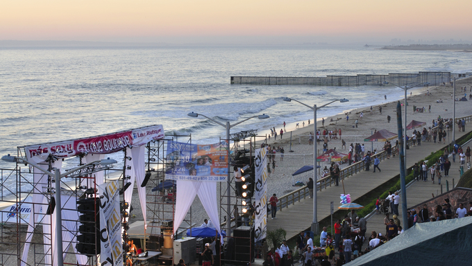 View of the Fourth Annual Tijuana Beach Festival with ocean and border fence in background at sunset.