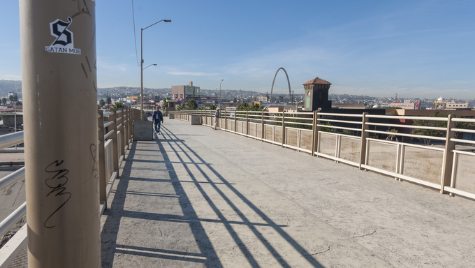 Downtown Tijuana arch is seen from the pedestrian bridge that crosses the Tijuana River on a clear sunny day.