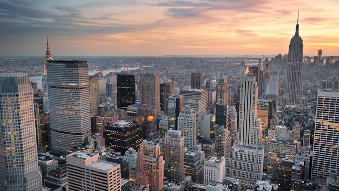 New York City skyline aerial view at sunset with colorful cloud and skyscrapers of midtown Manhattan.