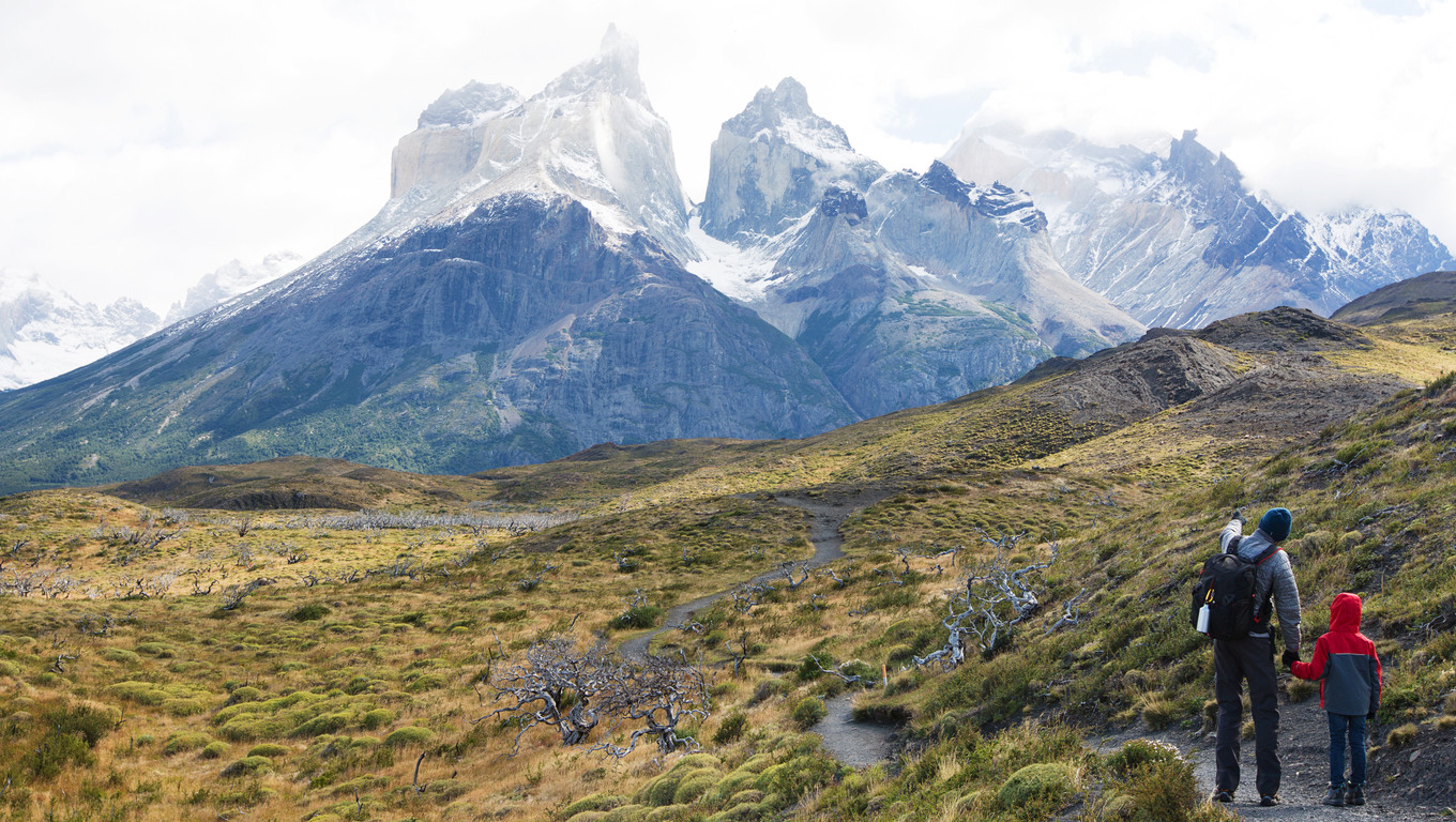 panorama of family enjoying active vacation and view of cuernos del paine, famous peaks in torres del paine national park, patagonia, chile