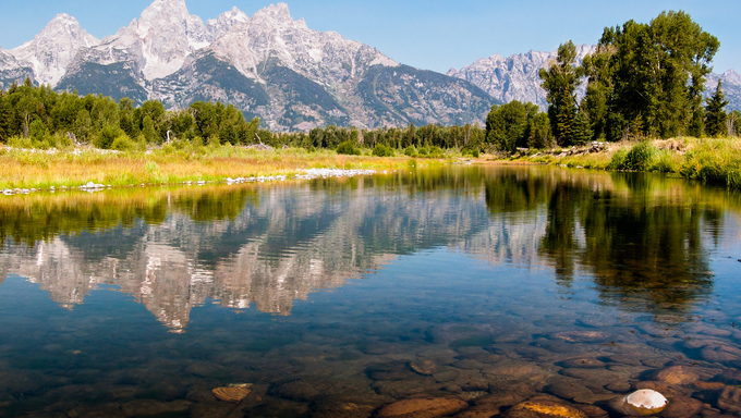 The Teton Mountain Range is reflected in the shallow and still waters of a braid of the Snake River in Grand Teton National park, Wyoming, USA. Near Kennewick, WA.