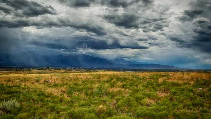 Looking across a field south east toward Draper Utah USA and Utah county under cloudy stormy sky' with the Wasatch mountains in view.