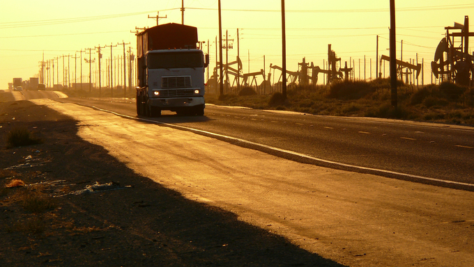 A Central California oil field highway, during a steamy hot sepia Summer sunset.