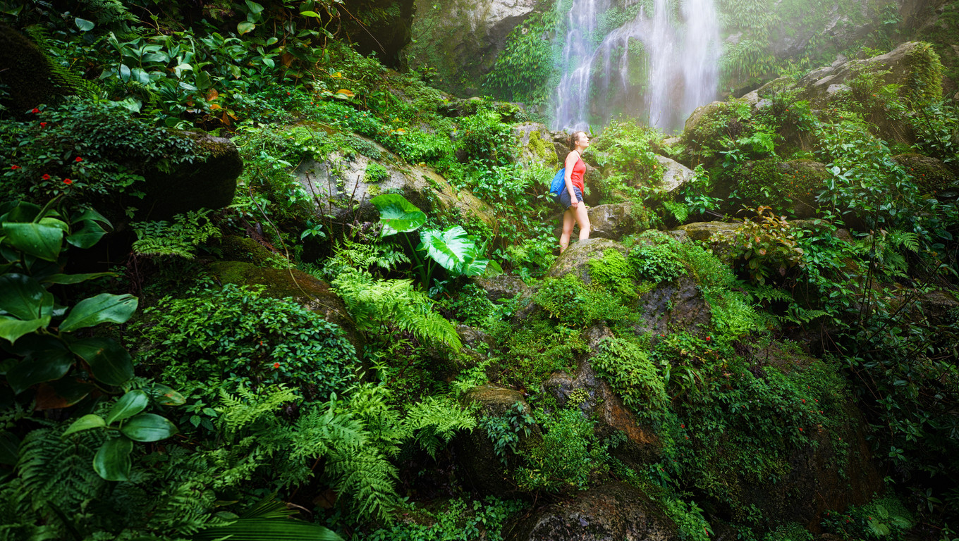 A tired but happy tourist woman looking at the waterfall in the Central America jungles