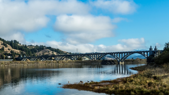 An arched bridge crosses the Rogue River in Gold Beach.