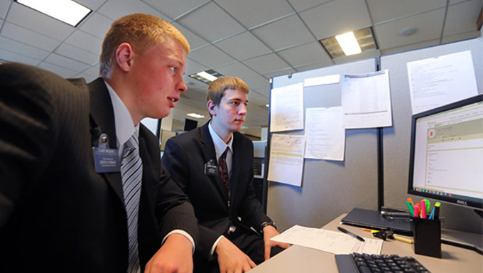 Elder Issac Maughan of Rexburg Idaho  trains Elder Ammon Taylor, of Allen Texas, in the missionary contact center as members of the Family and Church History Headquarters Mission work Friday, Sept. 4, 2015, at Temple Square in Salt Lake City.