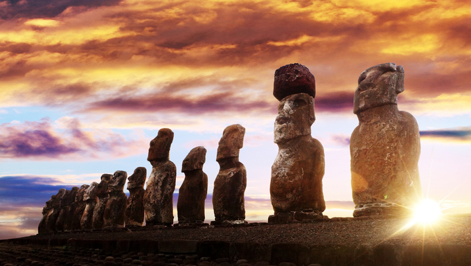 Standing moai in Easter Island against rising sun and orange sky