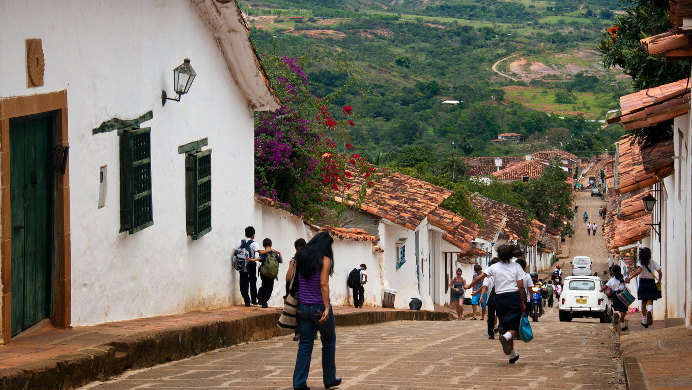 School children running the streets of the colonial village of Barichara, Santander, Colombia