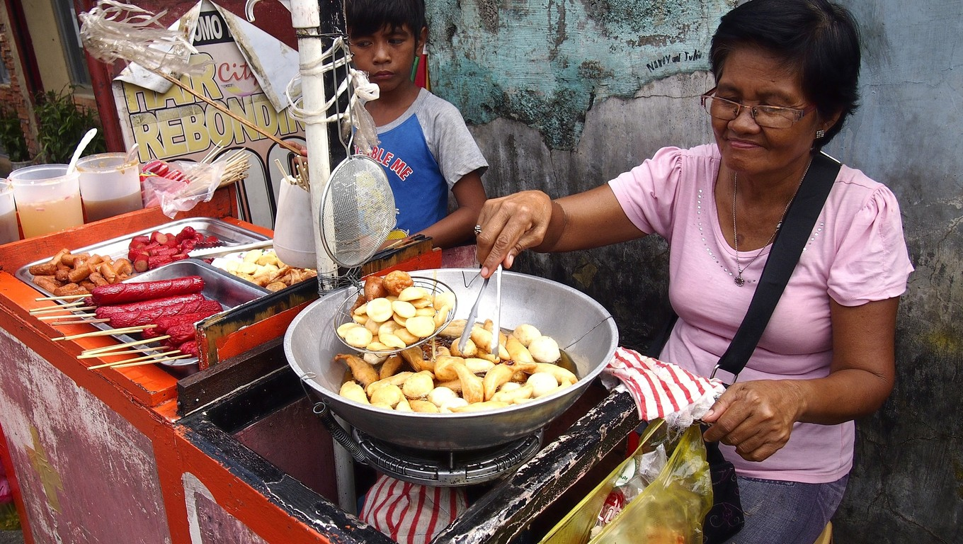 ANTIPOLO CITY, PHILIPPINES - JUNE 7, 2016: A mother and her son sell assorted street food in a cart along a street in the city of Antipolo, Philippines