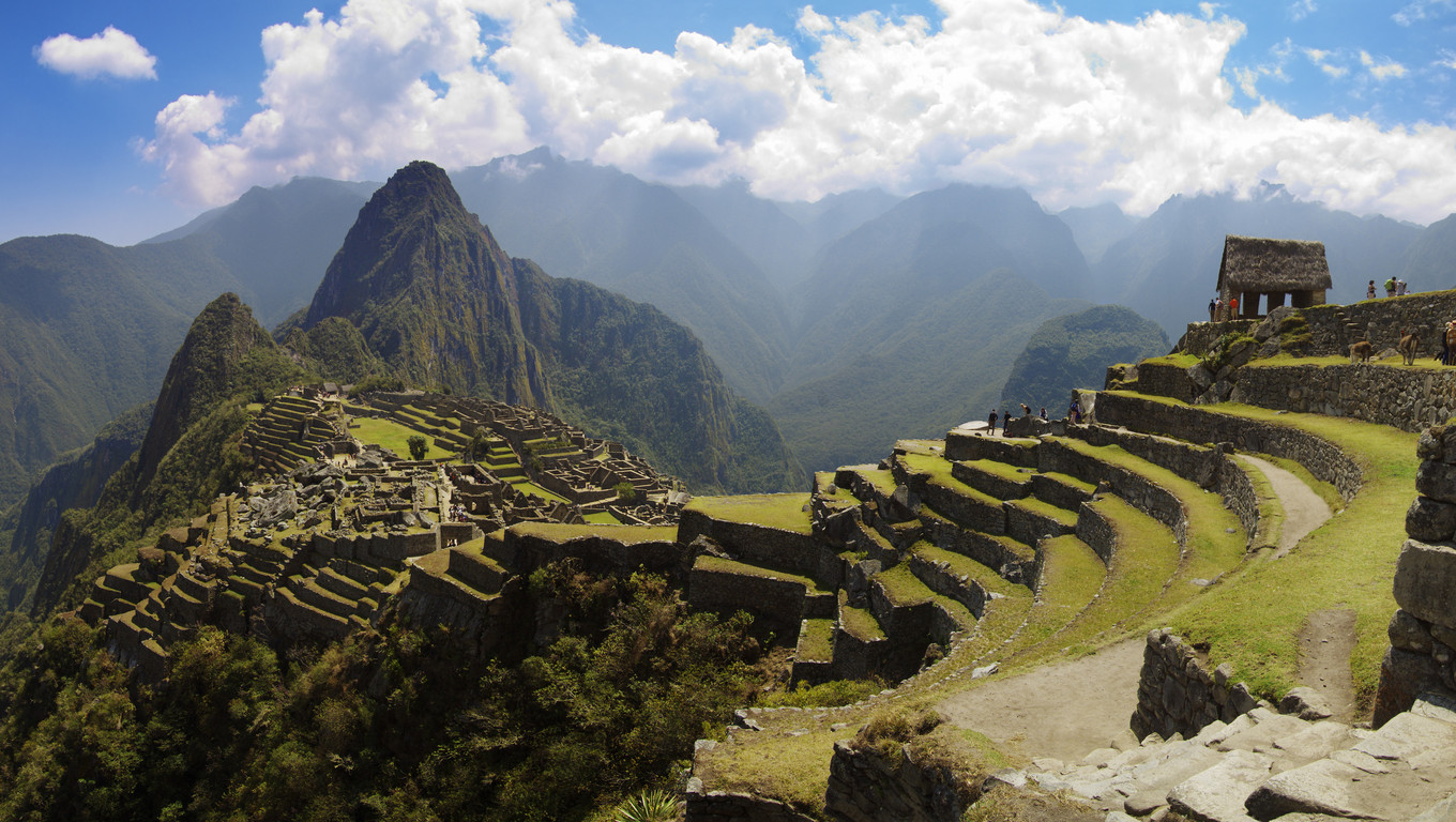 Panoramana of Machu Picchu, Guard house, agriculture terraces, Wayna Picchu and surrounding mountains in the background.