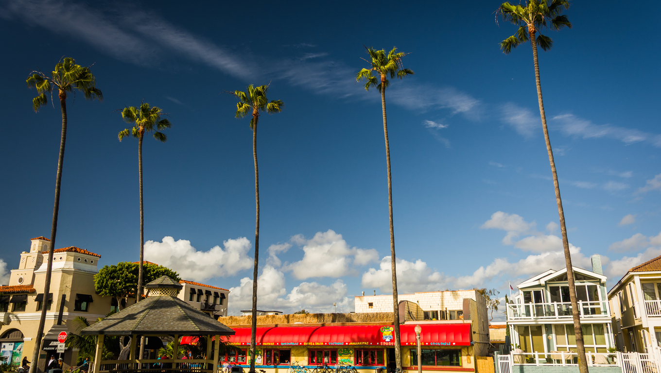 Palm trees and buildings along the boardwalk in Newport Beach, California.